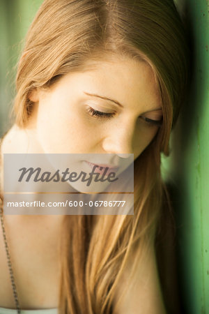 Close-up portrait of young woman with long hair outdoors, looking downwards Stock Photo - Premium Royalty-Free, Image code: 600-06786777