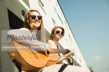 Young women sitting outdoors, hanging out and playing guitar, looking at camera, Mannheim, Germany Stock Photo - Premium Royalty-Free, Image code: 600-06786779