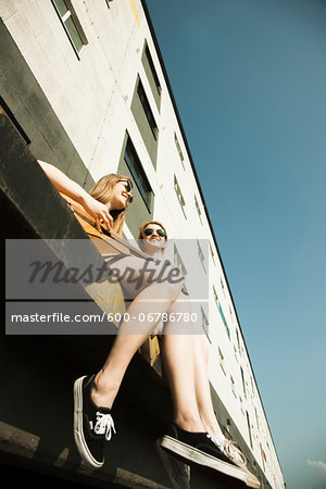 Young women sitting outdoors, hanging out and playing guitar, Mannheim, Germany Stock Photo - Premium Royalty-Free, Image code: 600-06786780