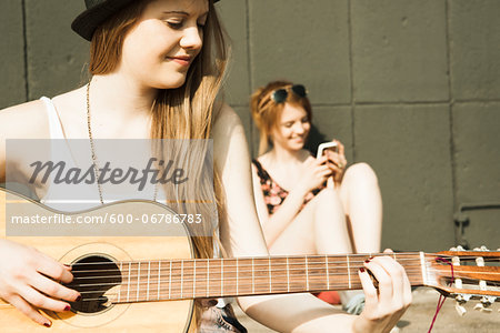 Young women sitting outdoors, hanging out and playing guitar, Mannheim, Germany Stock Photo - Premium Royalty-Free, Image code: 600-06786783