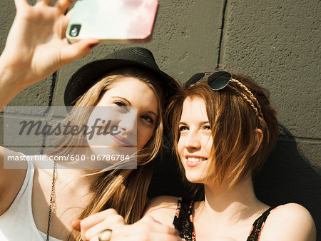 Close-up of young women taking photo of themselves with smart phone Stock Photo - Premium Royalty-Free, Image code: 600-06786784