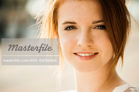 Close-up portrait of teenage girl outdoors, smiling at camera Stock Photo - Premium Royalty-Free, Image code: 600-06786805