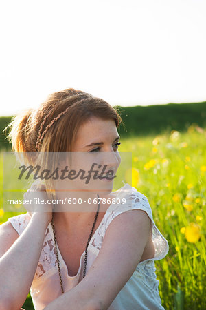 Portrait of teenage girl sitting in field, Germany Stock Photo - Premium Royalty-Free, Image code: 600-06786809
