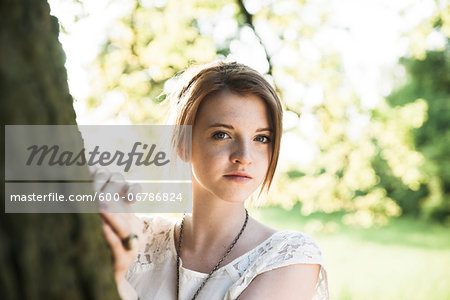 Portrait of teenage girl standing next to tree trunk, Germany Stock Photo - Premium Royalty-Free, Image code: 600-06786824