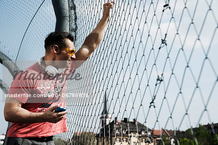 Mature man standing on outdoor basketball court holding MP3 player, Germany Stock Photo - Premium Royalty-Free, Image code: 600-06786836