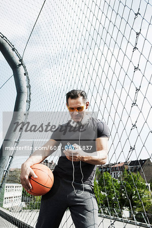 Mature man standing on outdoor basketball court holding basketball and looking at MP3 player, Germany Stock Photo - Premium Royalty-Free, Image code: 600-06786837