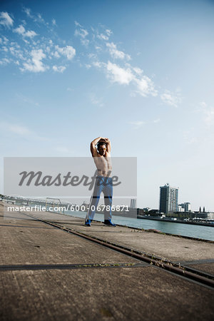 Mature man stretching on loading dock, Mannheim, Germany Stock Photo - Premium Royalty-Free, Image code: 600-06786871