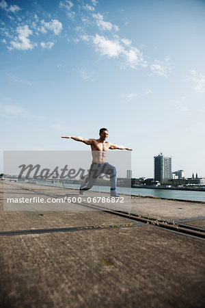 Mature man stretching on loading dock, Mannheim, Germany Stock Photo - Premium Royalty-Free, Image code: 600-06786872