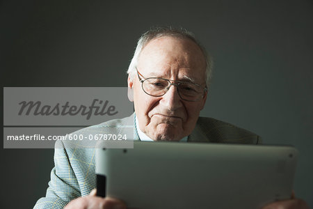 Elderly Man using Tablet Computer in Studio Stock Photo - Premium Royalty-Free, Image code: 600-06787024