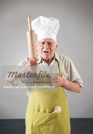 Elderly Man wearing Apron and Chef's Hat holding Rolling Pin in Studio Stock Photo - Premium Royalty-Free, Image code: 600-06787028