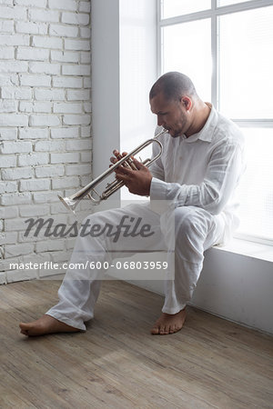 Portrait of Musician Playing Trumpet by Window, Italy Stock Photo - Premium Royalty-Free, Image code: 600-06803959