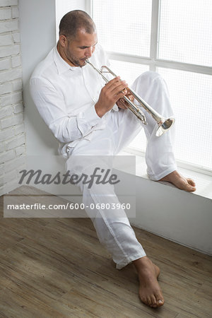 Portrait of Musician Playing Trumpet by Window, Italy Stock Photo - Premium Royalty-Free, Image code: 600-06803960