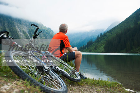 Mature Man Sitting by Lake with Mountain Bike, Vilsalpsee, Tannheim Valley, Tyrol, Austria Stock Photo - Premium Royalty-Free, Image code: 600-06819401