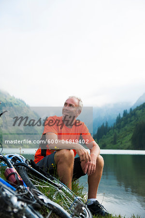 Mature Man Sitting by Lake with Mountain Bike, Vilsalpsee, Tannheim Valley, Tyrol, Austria Stock Photo - Premium Royalty-Free, Image code: 600-06819402
