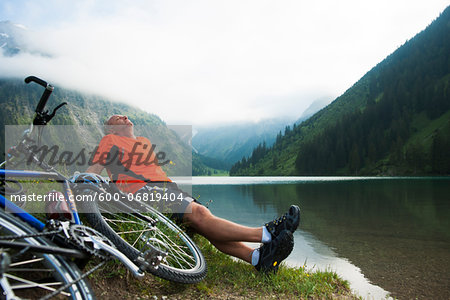 Mature Man Sitting by Lake with Mountain Bike, Vilsalpsee, Tannheim Valley, Tyrol, Austria Stock Photo - Premium Royalty-Free, Image code: 600-06819404