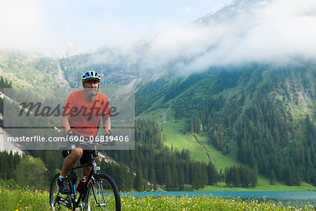 Mature Man Riding Mountain Bike by Vilsalpsee, Tannheim Valley, Tyrol, Austria Stock Photo - Premium Royalty-Free, Image code: 600-06819406