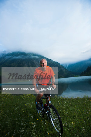 Mature Man Riding Mountain Bike by Vilsalpsee, Tannheim Valley, Tyrol, Austria Stock Photo - Premium Royalty-Free, Image code: 600-06819412