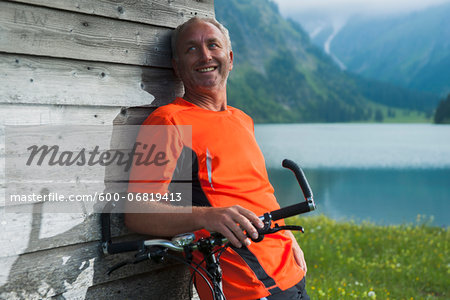 Mature Man leaning against Wooden Building with Mountain Bike, Vilsalpsee, Tannheim Valley, Tyrol, Austria Stock Photo - Premium Royalty-Free, Image code: 600-06819413