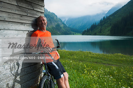 Mature Man leaning against Wooden Building with Mountain Bike, Vilsalpsee, Tannheim Valley, Tyrol, Austria Stock Photo - Premium Royalty-Free, Image code: 600-06819414