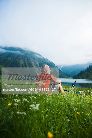 Mature Man with Mountain Bike sitting by Lake, Vilsalpsee, Tannheim Valley, Tyrol, Austria Stock Photo - Premium Royalty-Free, Image code: 600-06819417