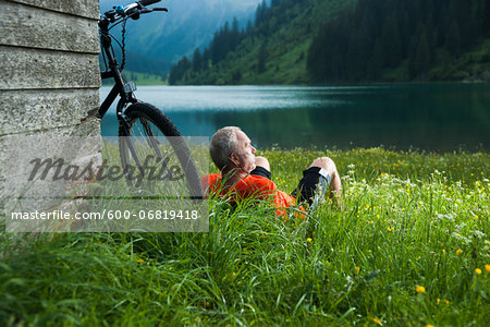 Mature Man with Mountain Bike Relaxing by Lake, Vilsalpsee, Tannheim Valley, Tyrol, Austria Stock Photo - Premium Royalty-Free, Image code: 600-06819418