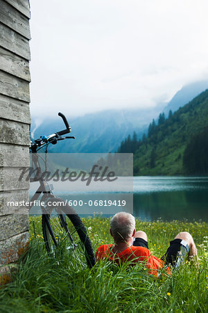 Mature Man with Mountain Bike Relaxing by Lake, Vilsalpsee, Tannheim Valley, Tyrol, Austria Stock Photo - Premium Royalty-Free, Image code: 600-06819419