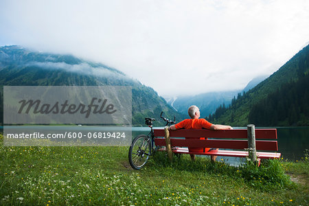 Mature Man on Bench by Lake with Mountain Bike, Vilsalpsee, Tannheim Valley, Tyrol, Austria Stock Photo - Premium Royalty-Free, Image code: 600-06819424