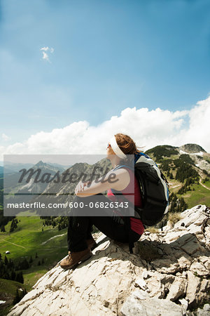 Mature woman sitting on cliff, hiking in mountains, Tannheim Valley, Austria