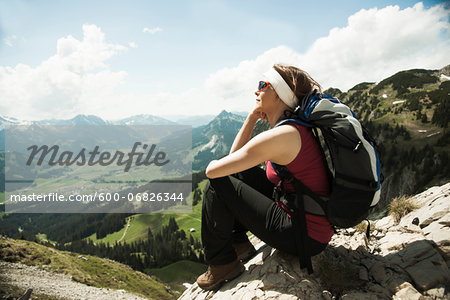 Mature woman sitting on cliff, hiking in mountains, Tannheim Valley, Austria Stock Photo - Premium Royalty-Free, Image code: 600-06826344