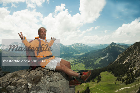 Mature man sitting on cliff with arms raised in air, hiking in mountains, Tannheim Valley, Austria Stock Photo - Premium Royalty-Free, Image code: 600-06826376