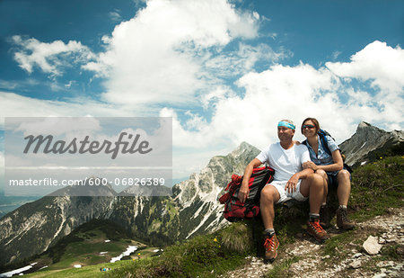 Mature couple sitting on grass, hiking in mountains, Tannheim Valley, Austria Stock Photo - Premium Royalty-Free, Image code: 600-06826389