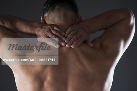 Close-up of Man with Hands on Back of his Neck, Studio Shot Stock Photo - Premium Royalty-Free, Image code: 600-06841744
