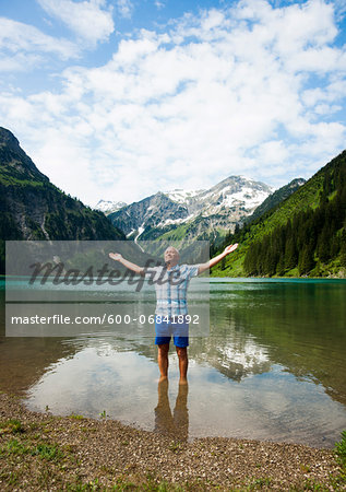 Mature man with arms stretched outward, standing in Lake Vilsalpsee, Tannheim Valley, Austria Stock Photo - Premium Royalty-Free, Image code: 600-06841892