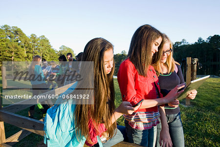 Group of pre-teens sitting on fence, looking at tablet computers and cellphones, outdoors, Florida, USA Stock Photo - Premium Royalty-Free, Image code: 600-06841922