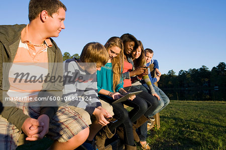 Group of pre-teens sitting on fence, looking at tablet computer and cellphones, outdoors, Florida, USA Stock Photo - Premium Royalty-Free, Image code: 600-06841924