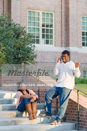 Young man and young woman outdoors on college campus steps, young man using smartphone, Florida, USA Stock Photo - Premium Royalty-Free, Image code: 600-06841938