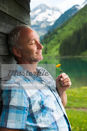 Portrait of mature man with eyes closed, holding flower, standing next to building at Lake Vilsalpsee, Tannheim Valley, Austria Stock Photo - Premium Royalty-Free, Image code: 600-06841947