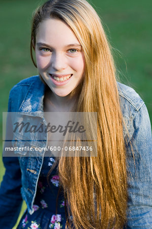 Portrait of pre-teen girl with long, blond hair, wearing jean jacket, outdoors Stock Photo - Premium Royalty-Free, Image code: 600-06847436