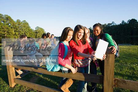 Group of pre-teens sitting on fence, looking at tablet computer and cellphones, outdoors Stock Photo - Premium Royalty-Free, Image code: 600-06847446