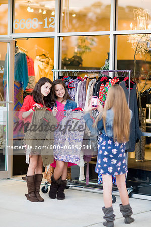 Pre-teen girls shopping for clothes and taking picture with smartphone Stock Photo - Premium Royalty-Free, Image code: 600-06892511