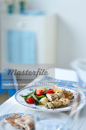 Greek Supper with Chicken Souvlaki, Green Beans, Tomatoes, Potatoes, Pita Bread, and Lemon Wedge on Table Stock Photo - Premium Royalty-Free, Image code: 600-06892687