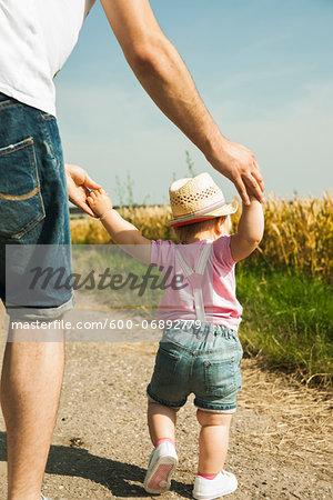 Father and Baby Daughter Walking Outdoors, Mannheim, Baden-Wurttemberg, Germany Stock Photo - Premium Royalty-Free, Image code: 600-06892779
