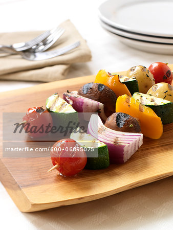 2 BBQ'd Veggie Kebabs on a cutting board ready to be served Stock Photo - Premium Royalty-Free, Image code: 600-06895075