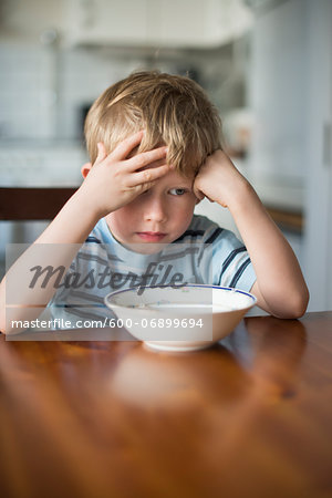 Young Boy with Hand on Head waiting for Breakfast at Kitchen Table, Copenhagen, Denmark Stock Photo - Premium Royalty-Free, Image code: 600-06899694