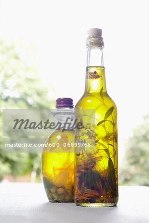 Still life of bottles of olive oil with herbs on window sill, Germany Stock Photo - Premium Royalty-Free, Image code: 600-06899766