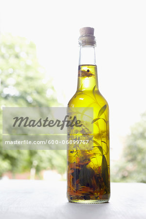 Still life of bottle of olive oil with herbs on window sill, Germany Stock Photo - Premium Royalty-Free, Image code: 600-06899767