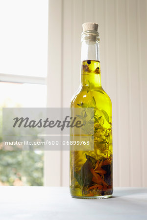 Still life of bottle of olive oil with herbs on window sill, Germany Stock Photo - Premium Royalty-Free, Image code: 600-06899768