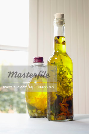 Still life of bottles of olive oil with herbs on window sill, Germany Stock Photo - Premium Royalty-Free, Image code: 600-06899769