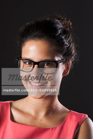 Portrait of teenage girl wearing horn-rimmed eyeglasses, smiling and looking at camera Stock Photo - Premium Royalty-Free, Image code: 600-06899814
