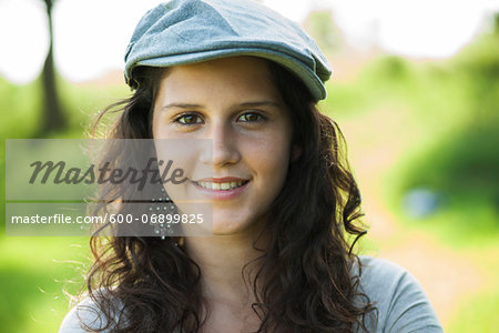 Close-up portrait of teenaged girl wearing cap outdoors, smiling and looking at camera, Germany Stock Photo - Premium Royalty-Free, Image code: 600-06899825